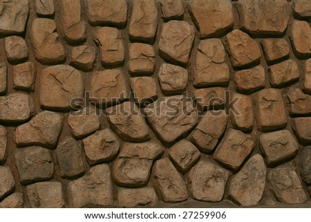 A brown rock wall with large stones.