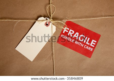 A brown shipping box with a blank tag and a fragile sticker with copy space - stock photo