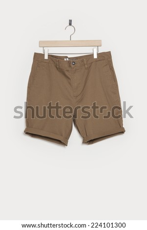 A brown short pants with wooden hanger isolated white. - stock photo