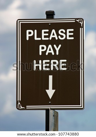 A brown sign reading Please Pay Here against a sunny sky - stock photo