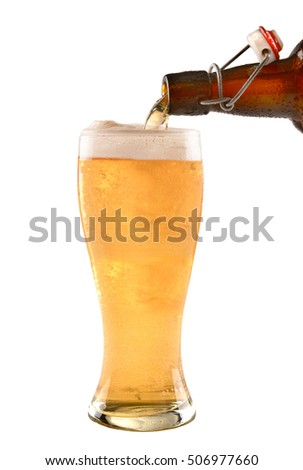 A brown swing top bottle of beer pouring into a glass on white.
