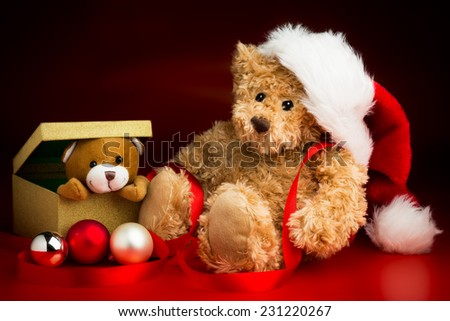 A brown teddy bear wearing a Christmas hat sitting next to a box with a teddy bear peeking out over the edge isolated against a red and black background and three baubles in front of them.