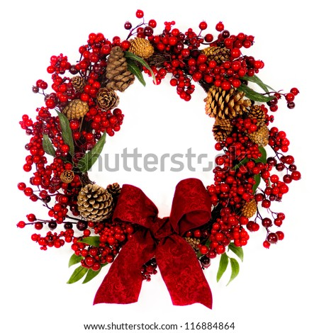 A brown twig wreath is decorated with red  berries, pine cones and a red damask bow. - stock photo