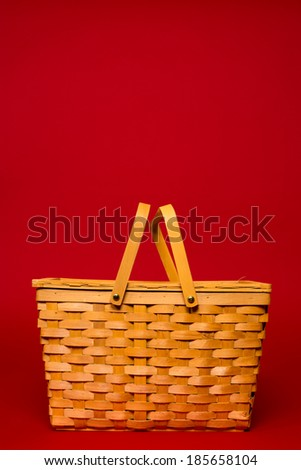 A brown wicker basket on a red background with copy space - stock photo