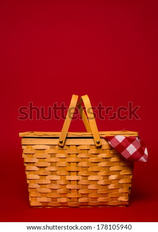 A brown, wicker picnic basket with red gingham tablecloth on a red background with copy space - stock photo