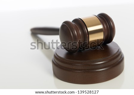A brown wooden judge's gavel on a white background