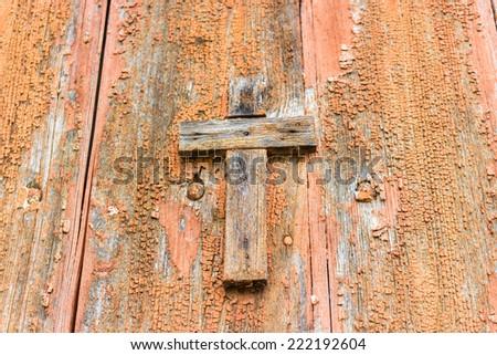 A brownish wooden Catholic cross nailed on grungy orange old wall - stock photo