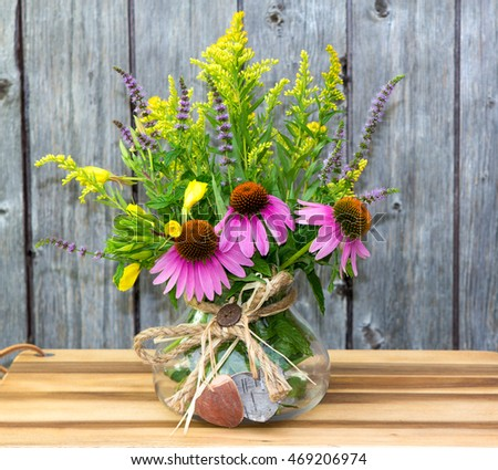 A brunch of Echinacea and Solidago blossoms in a clear glass, on a wooden table.