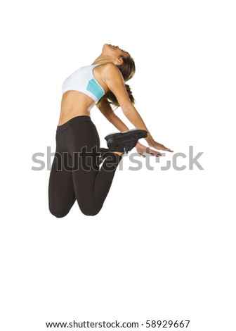A brunette fitness model jumping in the air as she works out - stock photo