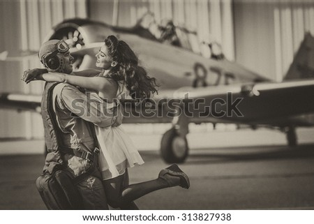 A brunette model in vintage clothing with a pilot and a WW II aircraft - stock photo