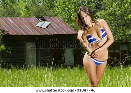 A brunette model posing in an outdoor environment wearing a striped blue bikini - stock photo