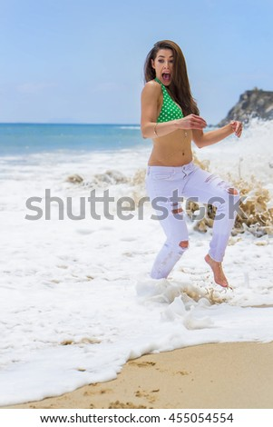 A brunette model running away from waves on a beach