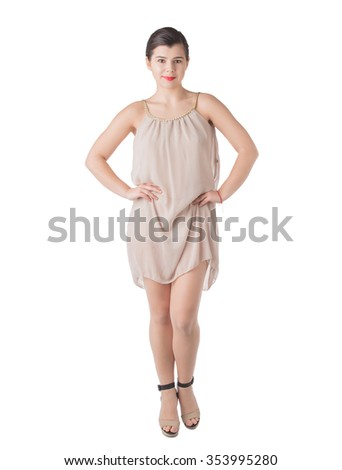 A brunette stands in high heels posing in short dress with arms akimbo isolated on white background