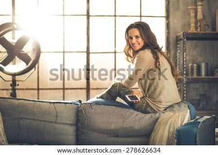A brunette woman is smiling with phone sitting on the back of a sofa. Industrial chic ambiance and cozy atmosphere, sunlight is streaming through the loft window. - stock photo