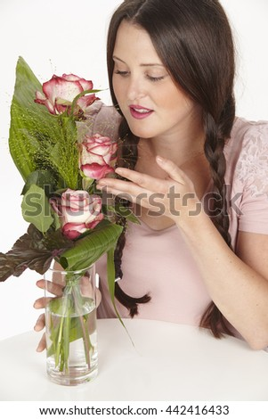 A brunette young woman with pigtails sits at a white table and touches a glass vase with a bouquet of white pink shaded roses.
