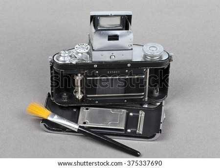 a brush and dusty old photo camera with open back cover - stock photo