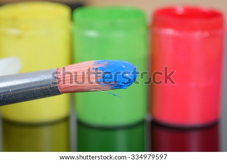 A brush with blue paint, three pots of yellow/green/red paint in the background