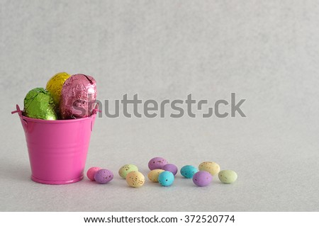A bucket filled with easter eggs and some small ones laying next to it isolated against a white background - stock photo