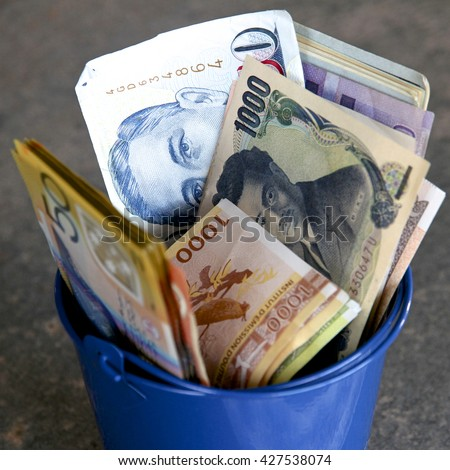 A bucket full of mixed currencies - stock photo