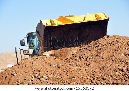 A bucket loader tackles a large dirt pile on a construction project - stock photo