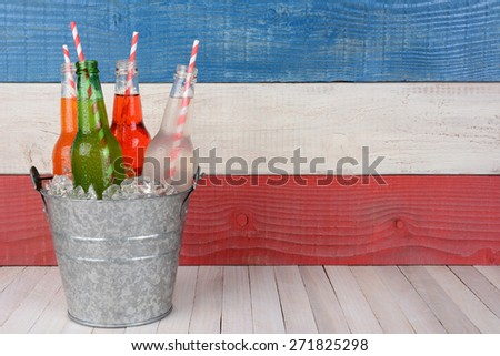 A bucket of soda bottles with drinking straws against a red, white and blue background for a 4th of July picnic, with copy space. - stock photo