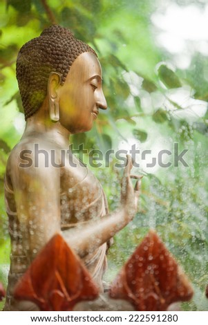 A Buddha bronze statue sit in the middle of a lush green forest at Vien Khong monastery, Vietnam - stock photo