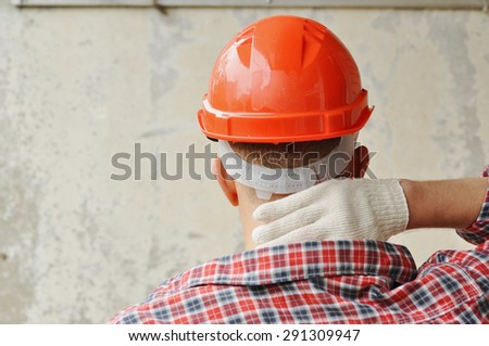 A builder in red helmet feels a Pain in a neck