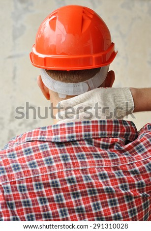 A builder in red helmet feels a Pain in a neck  - stock photo
