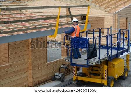 A builder installs a safety guard around the roof of a new building before the iron goes on - stock photo