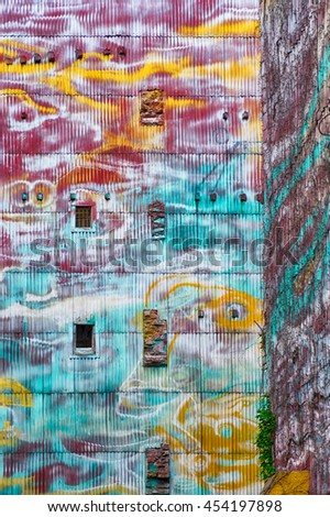 A building exterior painted in vivid, almost psychedelic, colors provides a bright background to an alley in Barcelona. - stock photo