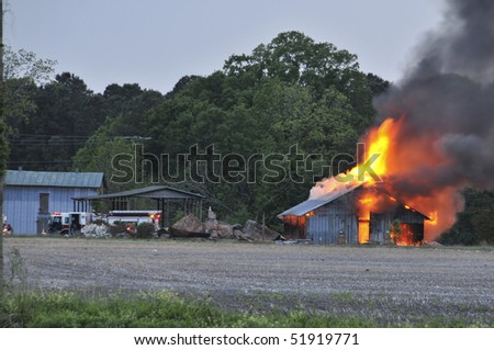 A building in the midst of being on fire - stock photo