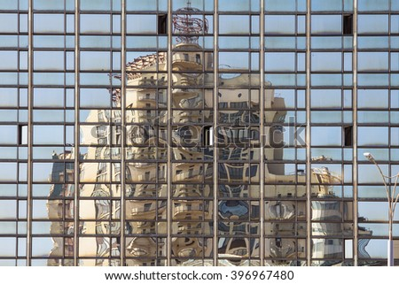A building that is reflected in the windows of another large building; the reflection is divided into curved pieces - stock photo
