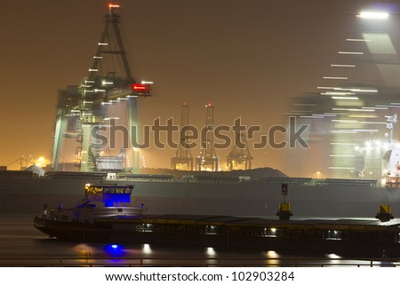 A bulk-carrier supplying cargo (iron-ore) and an inland canal vessel (foreground) in the port of Rotterdam - stock photo