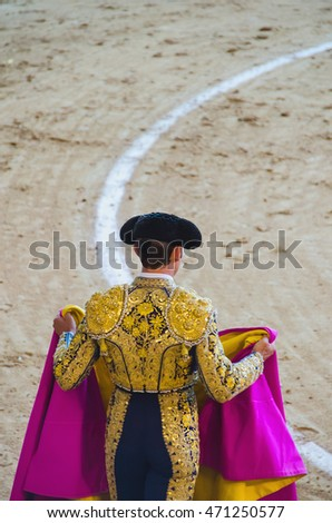 A bullfighter holding his capote and awaiting for the bull in the bullring. Corrida de toros