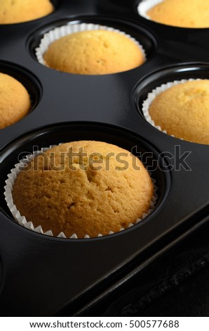 A bun tin filled with freshly baked golden vanilla cupcakes in paper cases, cooling on black slate.