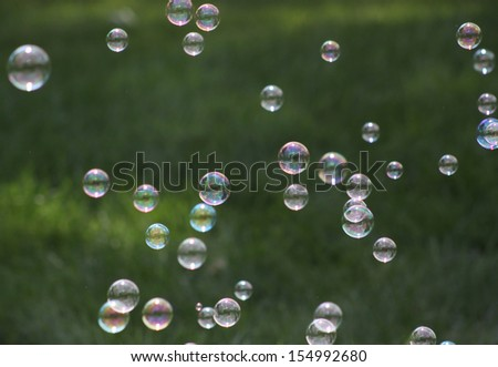 A bunch of bubbles floating over green grass - stock photo