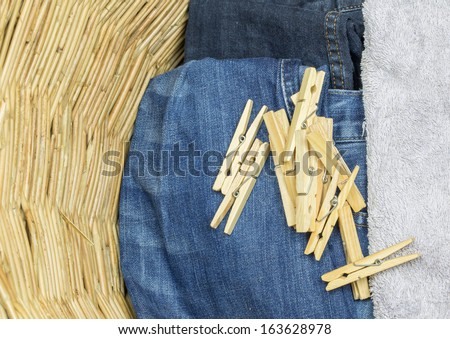 A bunch of clothes peg and laundry in a wicker basket - stock photo