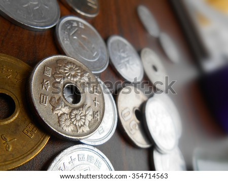 A Bunch of Coin Money Japanese Yen Currency on Brown Table..