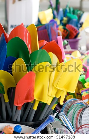 A bunch of colorful shovels in front of a dollar store.