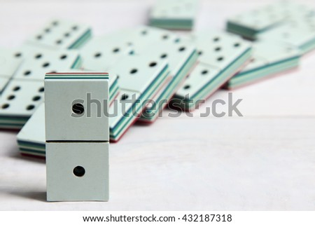 a bunch of dominoes lying on a white wooden background - stock photo
