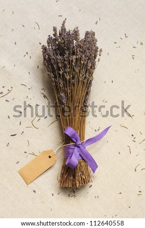 A bunch of dried lavender with blank card (tag) on linen canvas background - stock photo