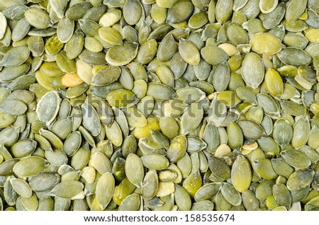A bunch of dry green pumpkin seeds - stock photo