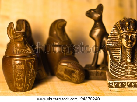 A bunch of egyptian figurines over papyrus paper background, selective depth of field. - stock photo