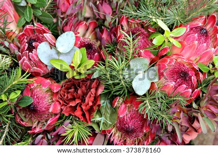 A bunch of flowers comprising of proteas and other plants. - stock photo