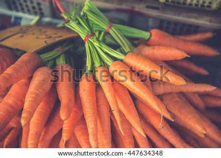 A bunch of fresh carrots on natural background  (Vintage filter effect used) - stock photo