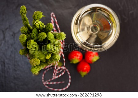 A bunch of fresh green Asparagus on Slate, with a glass of White Wine and Strawberries. Top Shot. - stock photo