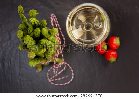 A bunch of fresh green Asparagus on Slate, with a glass of White Wine and Strawberries. Top Shot - stock photo