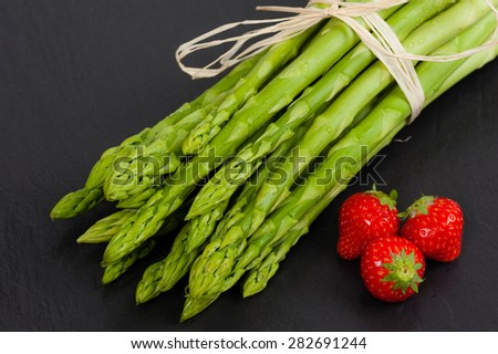 A bunch of fresh green Asparagus on Slate, with Strawberries - stock photo