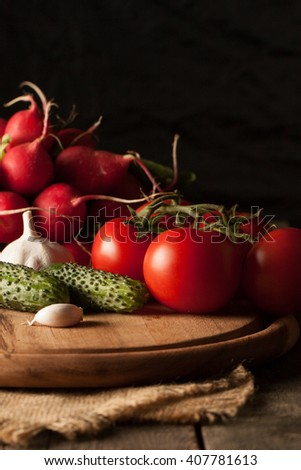 A bunch of fresh natural radish on dark board on wooden background, close up of radishes and different seasonal vegetables. Cucumbers, tomatoes and garlic