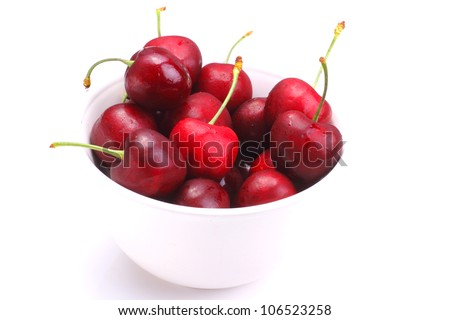 A bunch of fresh ripe cherries in a white bowl on white